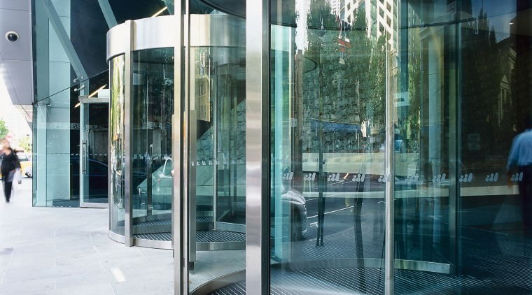 view of the glass revolving doors architecture, building, condominium, door, facade, glass, reflection, structure, window, white, teal, black