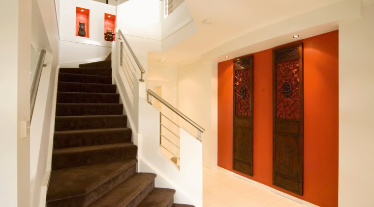 Stairwell with brown carpeted steps, cream walls and apartment, architecture, ceiling, daylighting, estate, floor, flooring, home, house, interior design, lobby, property, real estate, room, stairs, orange, brown
