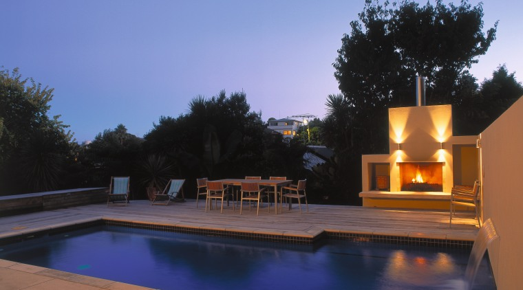 view of the outdoor entertainment area and mayfair backyard, estate, evening, home, house, lighting, property, real estate, reflection, residential area, roof, sky, swimming pool, villa, water, blue