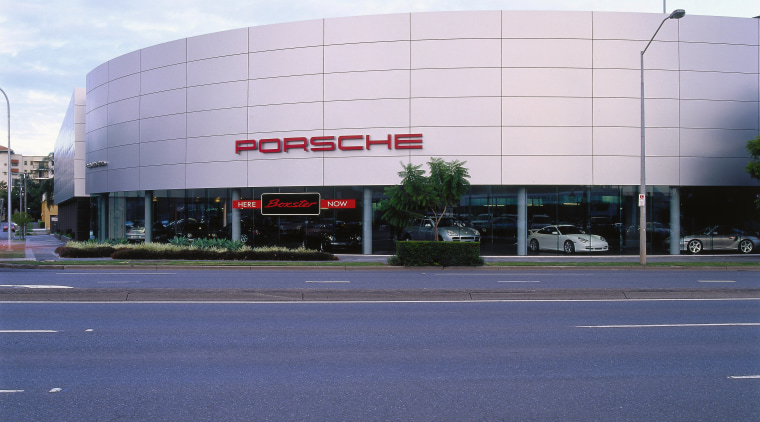 view of the porsche building will glazing and architecture, asphalt, building, commercial building, corporate headquarters, daytime, facade, headquarters, infrastructure, metropolitan area, sky, structure, white, blue