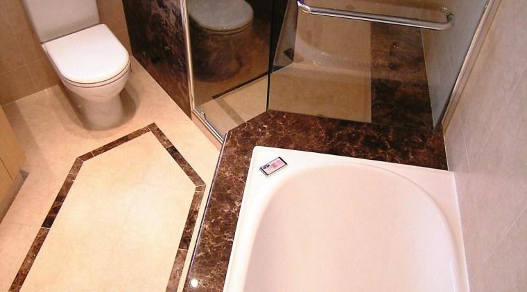 overhead view of the bathtub, showing brown stone bathroom, floor, plumbing fixture, property, room, sink, tile, toilet, toilet seat, orange, brown