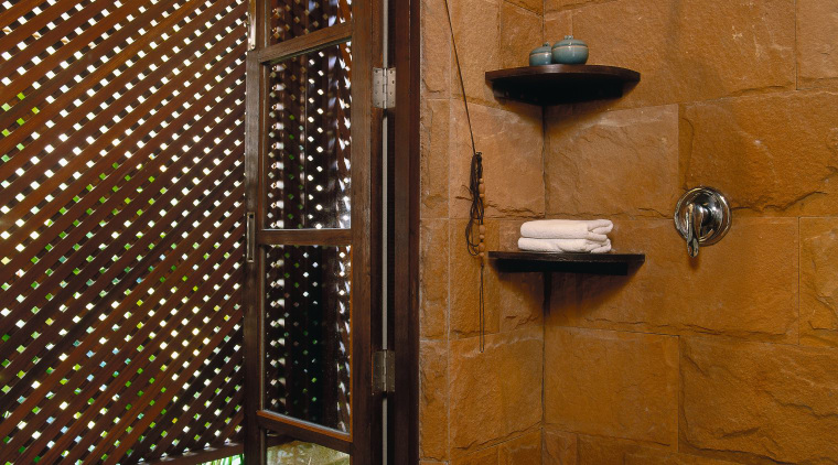 view of the bathroom featuring sandstone walls, glazed bathroom, interior design, room, tile, wall, brown