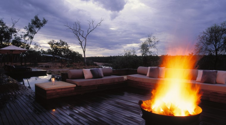 the outdoor seating area features an open fire backyard, campfire, evening, fire, heat, landscape, lighting, reflection, sky, sunlight, tree, water, water feature, black, purple