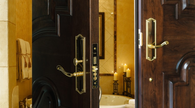 A view of two wooden doors with gold door, interior design, wood, black