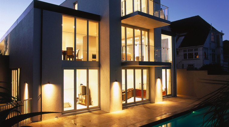 Exterior view of three level home, outdoor lighting, apartment, architecture, building, elevation, estate, facade, home, house, lighting, mixed use, property, real estate, reflection, residential area, villa, window, blue, black