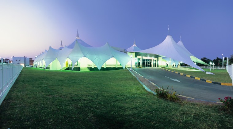 Exterior view of building featuring large canopy structure architecture, grass, landmark, plant, sky, structure, tree, blue