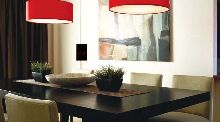 Dining room with two red lamp shades overhead. ceiling, chair, chandelier, dining room, furniture, interior design, lamp, light fixture, lighting, lighting accessory, product design, room, table, wall, window, white, black