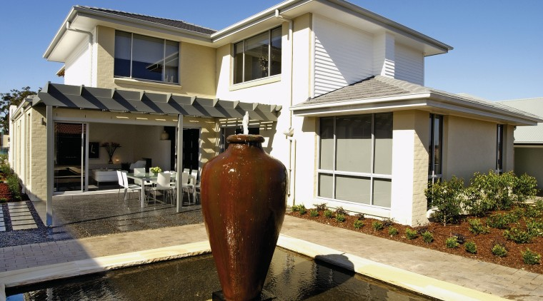 A view of the large water feature with building, facade, home, house, property, real estate, residential area, siding, window, brown
