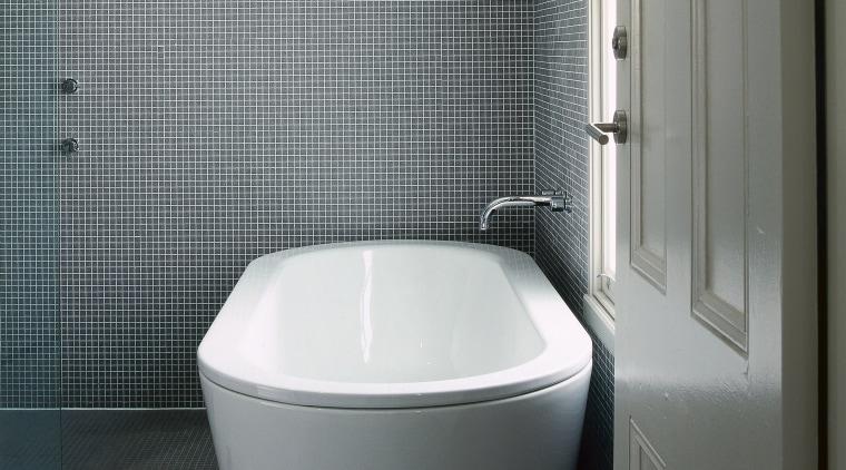 A view of a bthroom, tiled floor and bathroom, bathtub, bidet, plumbing fixture, product design, toilet, toilet seat, gray, black