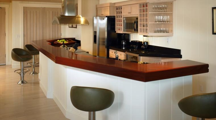 Kitchen with mahogony island countertop, black granite countertop, cabinetry, countertop, cuisine classique, floor, flooring, furniture, interior design, kitchen, room, brown, orange