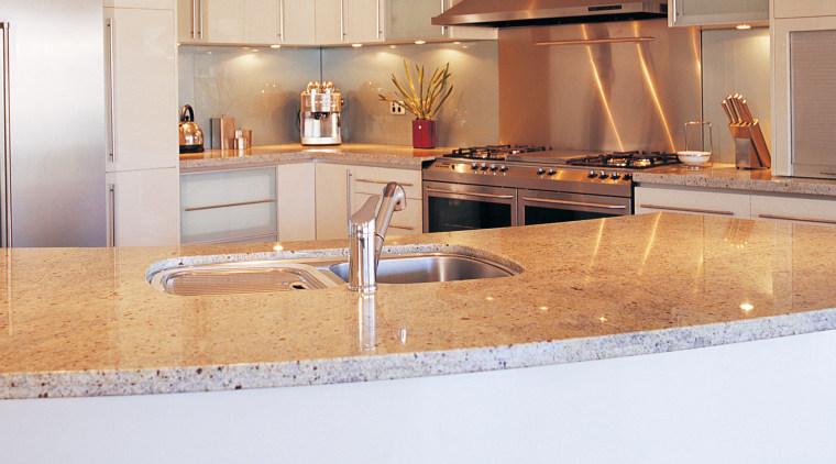Kitchen with curved granite island benchtop, stainless steel countertop, cuisine classique, floor, flooring, interior design, kitchen, under cabinet lighting, orange, white