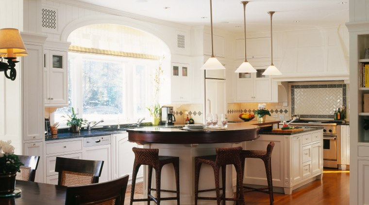 view of the kitchen  featuring large windows, cabinetry, ceiling, countertop, cuisine classique, dining room, floor, flooring, hardwood, home, interior design, kitchen, room, window, wood flooring, white