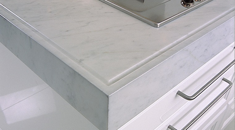 Closeup view of white Carrara benchtop with edge chest of drawers, countertop, drawer, floor, furniture, kitchen, product design, sink, table, tap, gray