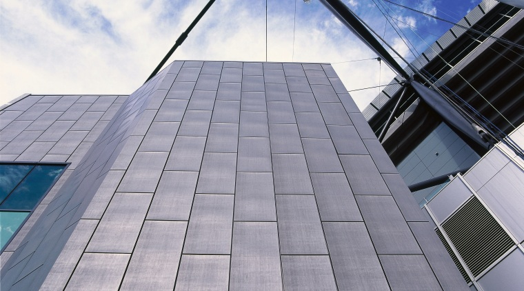 View of zinc panels on facade of stadium. architecture, building, cloud, daylighting, daytime, facade, line, roof, sky, skyscraper, structure, gray