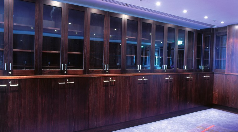 Room with dark timber cabinets along walls. light, lighting, blue