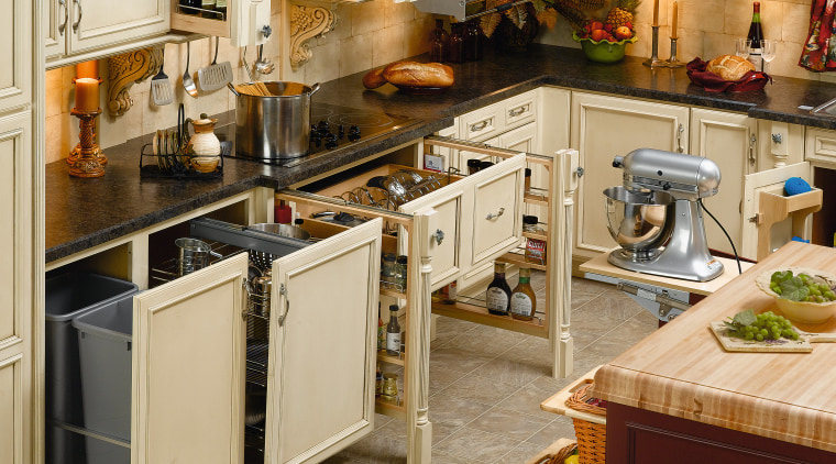 Traditional style kitchen with pull out storage systems. cabinetry, countertop, cuisine classique, floor, flooring, furniture, kitchen, room, brown, orange