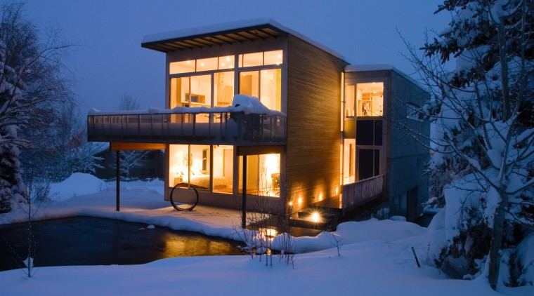 Image of the exterior of this beautiful home architecture, building, cottage, estate, evening, facade, home, house, lighting, property, real estate, residential area, sky, snow, villa, window, winter, blue