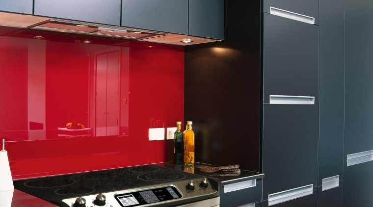 Kitchen with black cabinetry, red splashback, and cooktop cabinetry, countertop, home appliance, interior design, kitchen, product design, black, gray