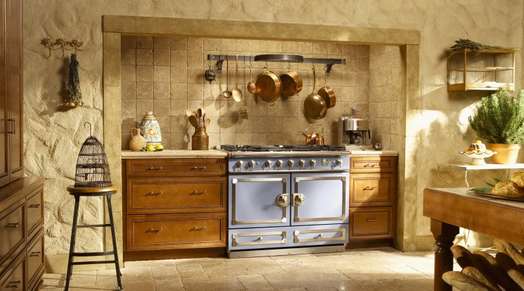 Traditional style kitchen with wood cabinetry, stone walls cabinetry, countertop, cuisine classique, furniture, interior design, kitchen, room, brown, orange