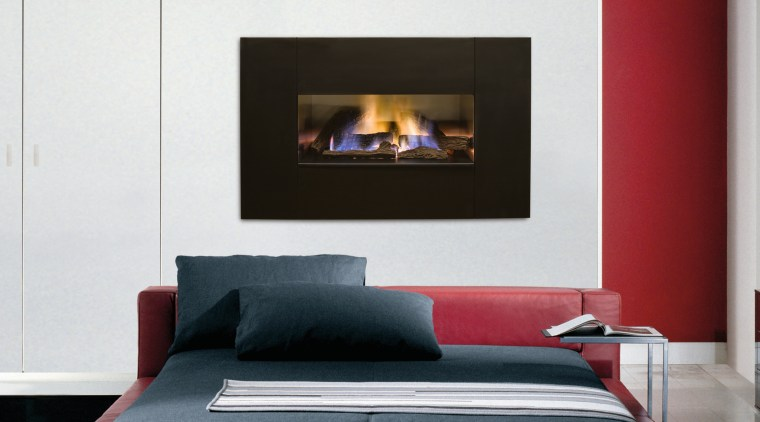 Fireplace with dark surround set into white wall, bed, bed frame, couch, fireplace, furniture, hearth, interior design, mattress, sofa bed, white