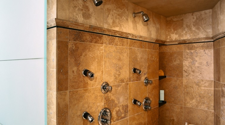 view of this bathrom featuring a noritz tankless bathroom, ceiling, floor, flooring, interior design, plumbing fixture, room, shower, tile, wall, brown
