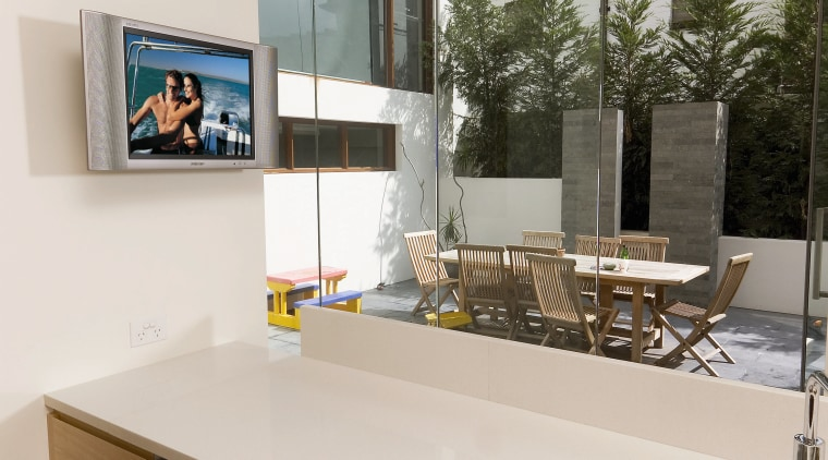 Kitchen with white benchtop, wall mounted tv screen, countertop, furniture, interior design, product design, table, white