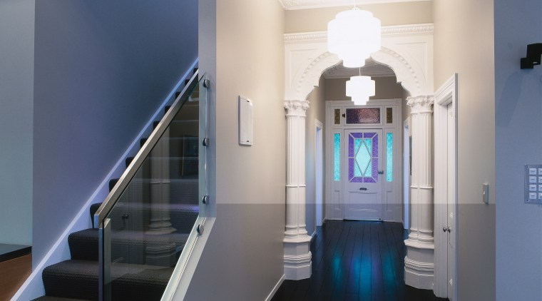 view of the renovated hallway featuring dark stained architecture, ceiling, daylighting, floor, handrail, home, interior design, property, real estate, stairs, structure, blue
