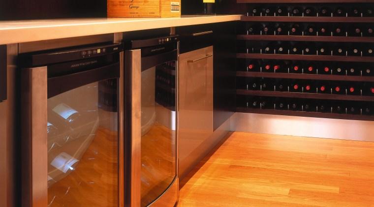 view of the wine cellar featuring dark wood floor, flooring, furniture, hardwood, interior design, light, lighting, table, wood, wood flooring, black, orange