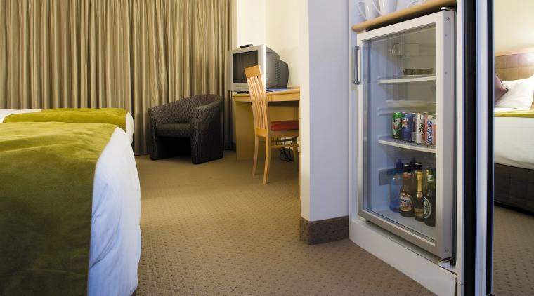 A view of a Haier mini fridge. bedroom, floor, flooring, furniture, interior design, real estate, room, suite, brown