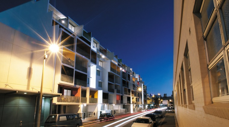 Exterior view of this new apartment development featuring apartment, architecture, building, car, city, commercial building, condominium, downtown, evening, facade, infrastructure, lighting, metropolis, metropolitan area, mixed use, neighbourhood, night, real estate, residential area, road, sky, street, town, urban area, blue