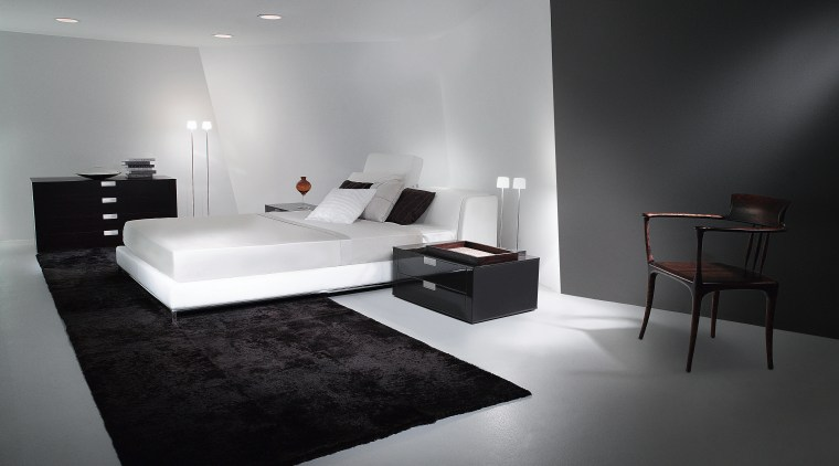 Bedroom with white bed and bedding, black rug, architecture, bed, bed frame, bedroom, black and white, floor, furniture, interior design, product design, room, table, wall, gray, black