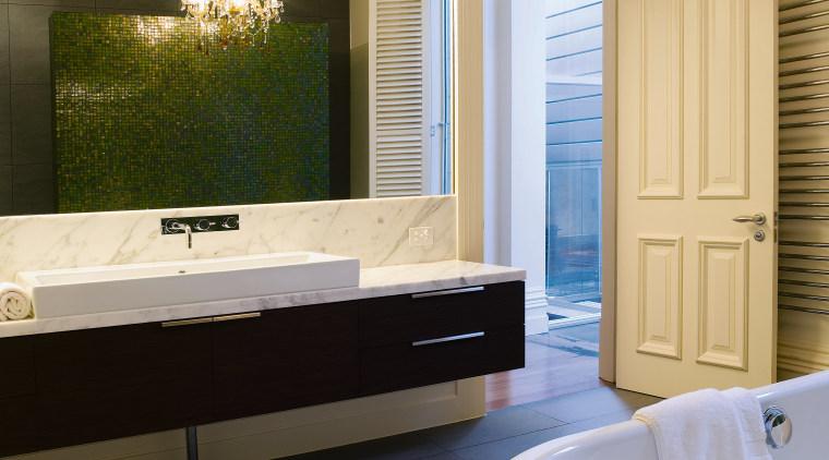 A wall-hung vanity is a contemporary feature that bathroom, bathtub, floor, flooring, home, interior design, room, window, orange