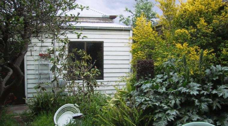 A view of the home before it was backyard, cottage, garden, home, house, outdoor structure, plant, property, real estate, shed, shrub, tree, yard