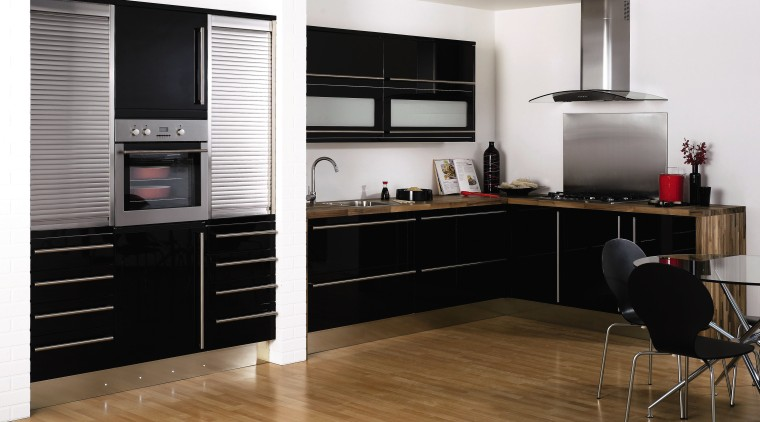 View of this modern kitchen featuring Stainless steel cabinetry, countertop, floor, flooring, furniture, home appliance, interior design, kitchen, white, black