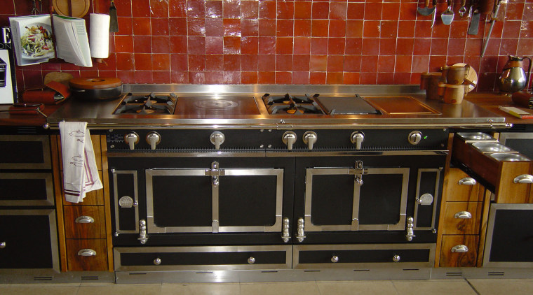 A view of a cooker from La Cornue. cabinetry, countertop, floor, flooring, furniture, hearth, home appliance, kitchen, kitchen appliance, kitchen stove, oven, stove, brown, black, red