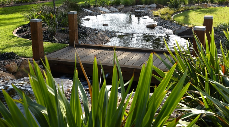 View of this timber boardwalk bridge crossing the backyard, flower, garden, grass, landscape, landscaping, outdoor structure, plant, pond, water, water feature, brown