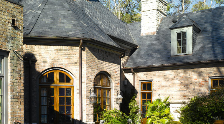 Exterior view of stone clad home with grey building, cottage, estate, facade, home, house, mansion, outdoor structure, real estate, residential area, roof, sky, tree, window