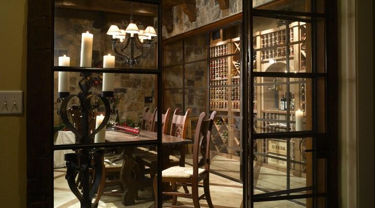 View of wine cellar with stone floor and door, furniture, interior design, lobby, window, brown