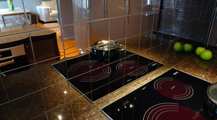 A vie wof some alloy kitchen tiles by countertop, floor, flooring, interior design, kitchen, room, under cabinet lighting, black