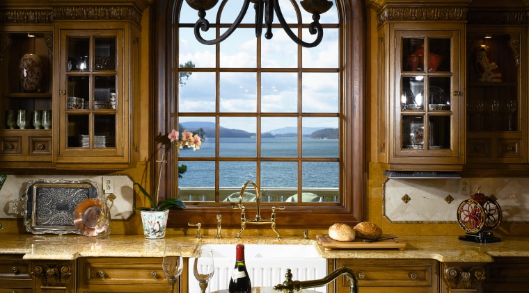 A view of this elegant kitchen featuring gold cabinetry, ceiling, countertop, estate, home, interior design, kitchen, lighting, room, window, brown
