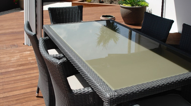 View of the outdoor dining area featuring table, chair, floor, flooring, furniture, outdoor furniture, table, wicker, black