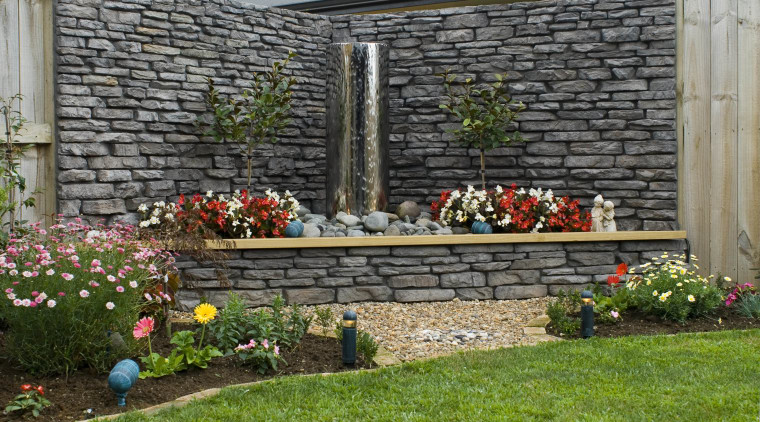 A view of a garden wall made out backyard, flower, garden, home, landscape, landscaping, outdoor structure, plant, stone wall, walkway, wall, yard, gray