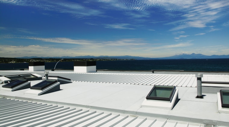 A view of a low pitched grey steel daylighting, deck, roof, sky, water, yacht, white