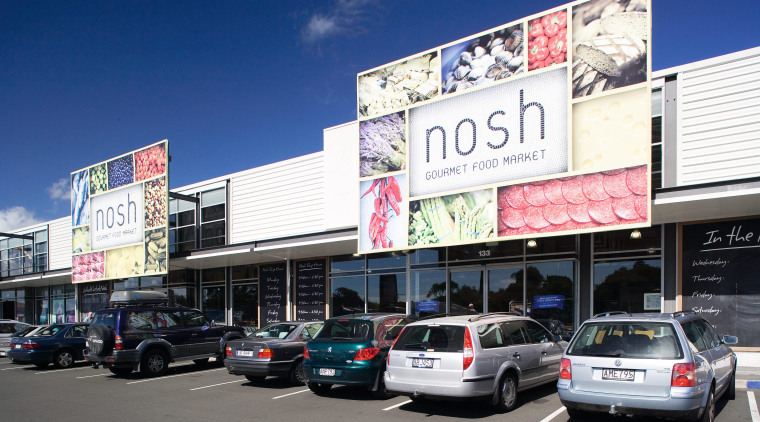 A view of this block of retail premises advertising, billboard, building, car, city, compact car, downtown, family car, luxury vehicle, real estate, sedan, signage, vehicle, blue, white