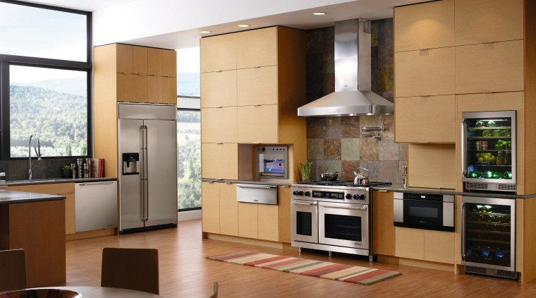 A view of this kitchen featuring timber veneer cabinetry, countertop, cuisine classique, floor, hardwood, home appliance, interior design, kitchen, living room, room, brown, gray