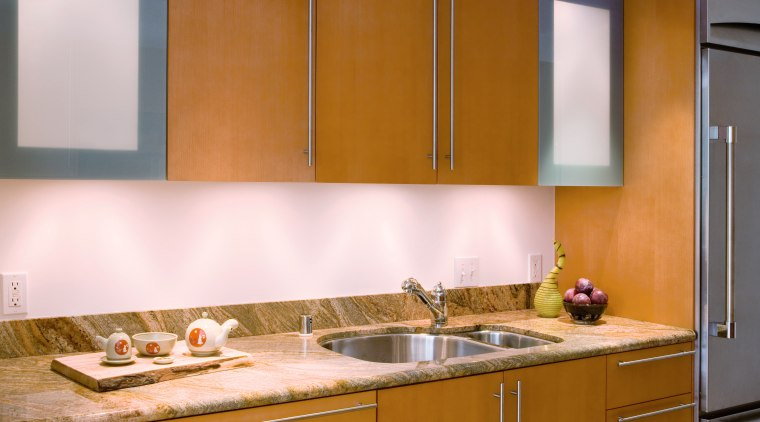 A view of this kitchen featuring stained timber cabinetry, countertop, interior design, kitchen, room, sink, under cabinet lighting, brown, white