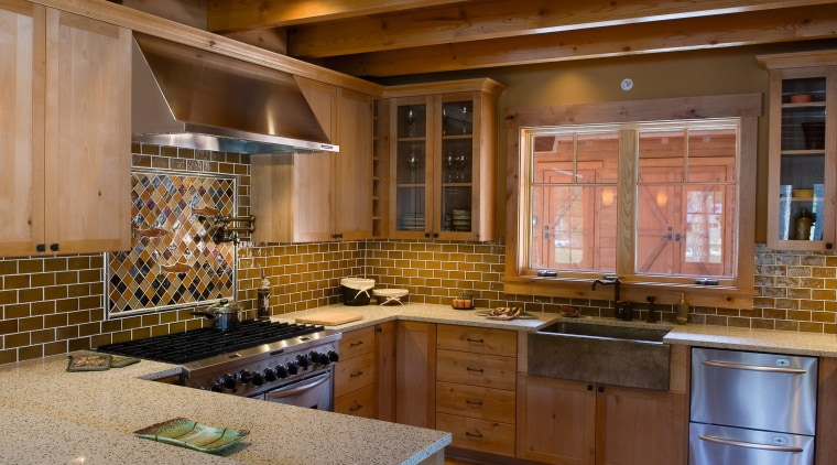 A view of this kitchen featuring stainless steel cabinetry, countertop, cuisine classique, flooring, interior design, kitchen, real estate, under cabinet lighting, brown