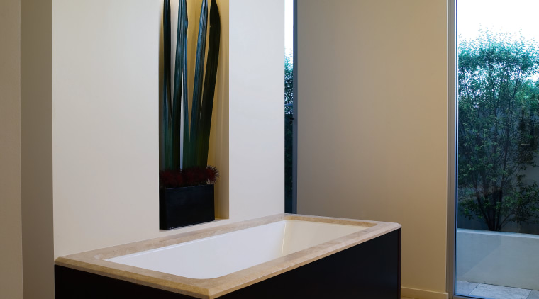 The tub fills from a ceiling-mounted pourer and floor, furniture, interior design, room, table, brown, gray