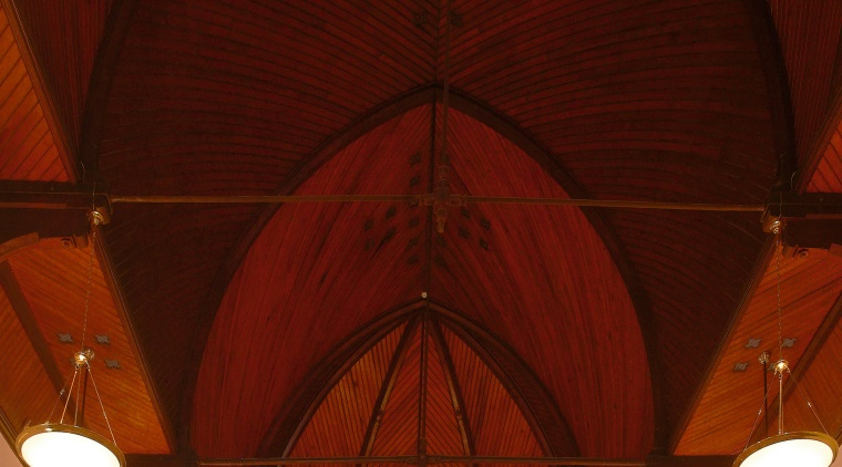 A view of this protected heritage church at arch, architecture, ceiling, chandelier, chapel, light, light fixture, lighting, lighting accessory, symmetry, wood, red, brown