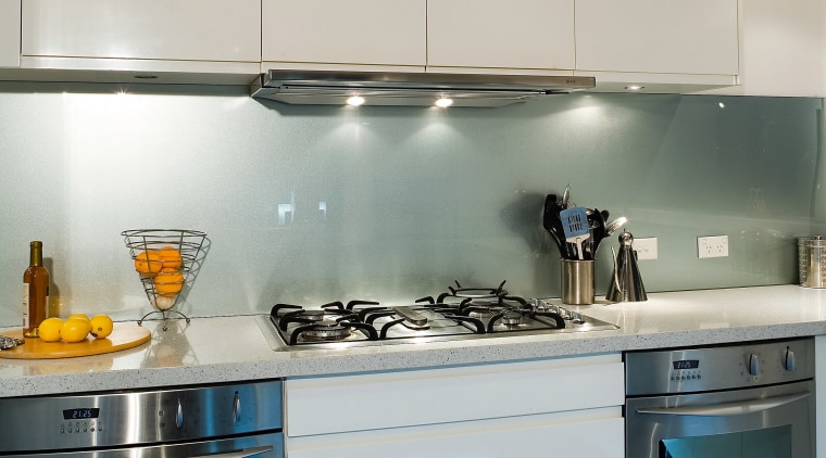 A view of this kitchen featuring tiled flooring, countertop, glass, interior design, kitchen, major appliance, room, under cabinet lighting, gray